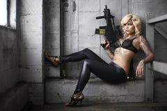 Mujer con estilo con el arma del asalto Foto de archivo libre de regalías