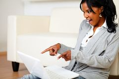 Mujer con estilo emocionada que señala la pantalla de la computadora portátil Fotografía de archivo