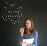 Mujer con estrategia del fútbol americano de la pluma en la pizarra Imagen de archivo libre de regalías