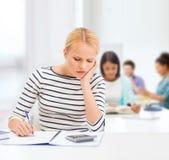 Mujer con estudiar del cuaderno y de la calculadora Imágenes de archivo libres de regalías