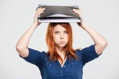 Mujer con exceso de trabajo agotada que se coloca con las carpetas en su cabeza Foto de archivo libre de regalías