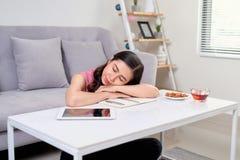 Mujer con exceso de trabajo cansada que descansa mientras que ella trabajaba la escritura no imagen de archivo libre de regalías