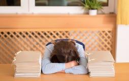 Mujer con exceso de trabajo que miente entre los documentos en oficina Imagenes de archivo