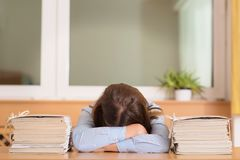 Mujer con exceso de trabajo que miente entre los documentos en oficina Imagen de archivo