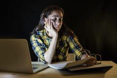Mujer con exceso de trabajo y cansada del estudiante que estudia tarde en la noche en fondo negro Fotografía de archivo