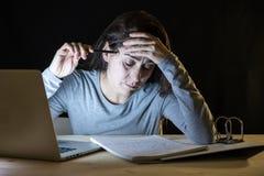 Mujer con exceso de trabajo y cansada del estudiante que estudia tarde en la noche en fondo negro Imagen de archivo
