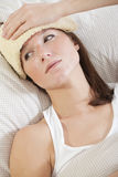 Mujer con fiebre en cama Imagenes de archivo
