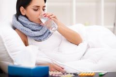 Mujer con fríos enfermos del termómetro, gripe, fiebre, dolor de cabeza en cama foto de archivo libre de regalías