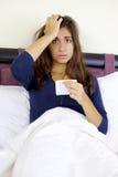 Mujer con gripe en la cama que toma medicing Foto de archivo libre de regalías