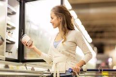 Mujer con helado en el congelador del colmado foto de archivo