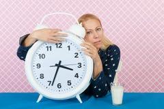Mujer con insomnio y el despertador grande Imagen de archivo