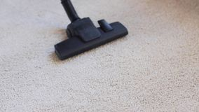 Mujer con la alfombra de la limpieza del aspirador en casa almacen de video