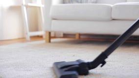 Mujer con la alfombra de la limpieza del aspirador en casa