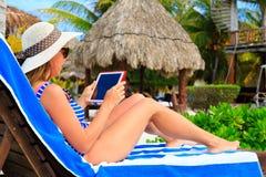 Mujer con la almohadilla táctil en vacaciones tropicales Imágenes de archivo libres de regalías
