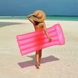 Mujer con la balsa inflable rosada en la playa Fotografía de archivo