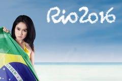 Mujer con la bandera del Brasil y el texto de Río 2016 Imágenes de archivo libres de regalías