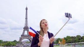 Mujer con la bandera francesa cerca de la torre Eiffel que hace el selfie Mujer turística sonriente que viaja en Europa almacen de video