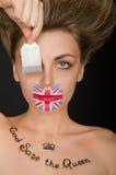 Mujer con la bandera inglesa en cara y la bolsita de té Foto de archivo