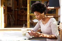 Mujer con la bebida en el café al aire libre usando el teléfono móvil Foto de archivo