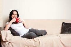 Mujer con la bebida en el sofá Imagenes de archivo