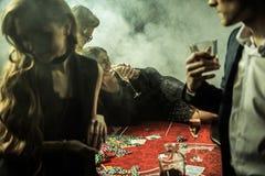Mujer con la bebida que miente en la tabla del póker durante juego en casino imagen de archivo libre de regalías