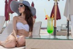 Mujer con la bebida tropical que se relaja en el complejo playero Fotografía de archivo libre de regalías