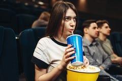 Mujer con la bebida y las palomitas que se sientan en cine Foto de archivo libre de regalías