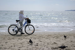 Mujer con la bici en la playa Imagen de archivo libre de regalías