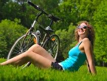Mujer con la bici en parque Imagen de archivo libre de regalías