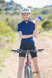 Mujer con la bici que sostiene el embotellador Fotografía de archivo