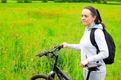 Mujer con la bicicleta en campo Imagen de archivo
