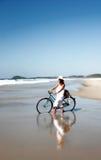 Mujer con la bicicleta en la playa Imágenes de archivo libres de regalías