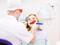 Mujer con la boca abierta que recibe el proc de sequía de relleno dental Imágenes de archivo libres de regalías