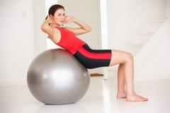 Mujer con la bola de la gimnasia en la gimnasia casera Fotografía de archivo