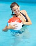 Mujer con la bola de playa en piscina Foto de archivo
