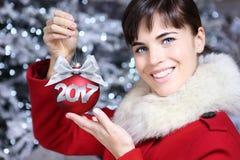 Mujer con la bola del rojo de la Navidad Fotografía de archivo libre de regalías