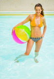 Mujer con la bola que se coloca en piscina Foto de archivo libre de regalías