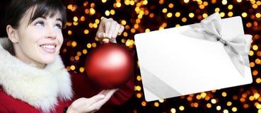 Mujer con la bola roja de la Navidad y carte cadeaux en luces de oro Fotografía de archivo libre de regalías