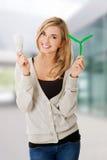 Mujer con la bombilla y el molino de viento llevados Imagen de archivo