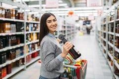 Mujer con la botella de bebida alcohólica en tienda imagen de archivo
