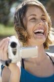 Mujer con la cámara de vídeo. Fotos de archivo libres de regalías