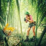 Mujer con la cámara del vintage en las zonas tropicales Foto de archivo libre de regalías