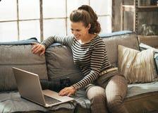 Mujer con la cámara moderna de la foto del dslr usando el ordenador portátil Imagenes de archivo