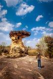 Mujer con la cámara que coloca la formación de roca cercana imágenes de archivo libres de regalías