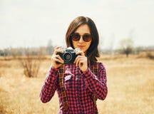 Mujer con la cámara vieja de la foto en el otoño al aire libre Imagenes de archivo