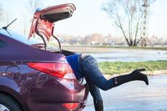 Mujer con la cabeza que consigue en el tronco de coche abierto Foto de archivo libre de regalías