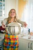 Mujer con la cacerola de la salsa interior Foto de archivo