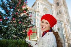 Mujer con la caja de regalo que coloca el árbol de navidad cercano en Florencia Fotografía de archivo libre de regalías