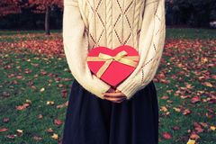 Mujer con la caja en forma de corazón en parque Fotografía de archivo libre de regalías