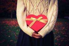 Mujer con la caja en forma de corazón en parque Fotografía de archivo